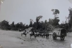 Carretas puxadas à bois atravessando rio